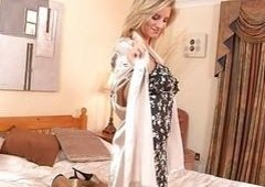 Sensual bigtitted blondie strips in a hotel room on a bed
