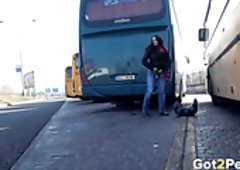 Darksome haired filthy sweetheart pisses backwards of big bus